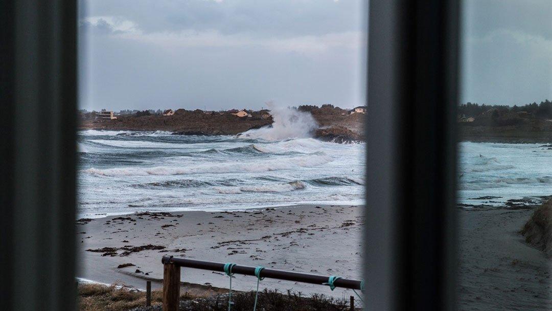 Bølger slår mot fjell og strand på Ferkingstad